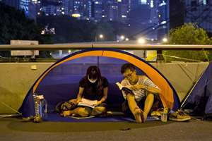 A couple read inside their tent at the occupied area in Central, Hong Kong. As thousands of protesters block city streets demanding democratic reforms, the future of Hong Kong's exclusive — some would say purposefully opaque — election committee may prove key to defusing a high-stakes political standoff that has dragged on for nearly a month.
