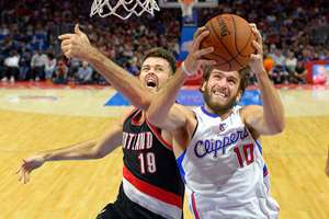 Los Angeles Clippers forward Spencer Hawes, right, goes to the basket as Portland Trail Blazers center Joel Freeland, of England, defends during the second half of a preseason NBA basketball game, in Los Angeles. The Trail Blazers won 99-89.
