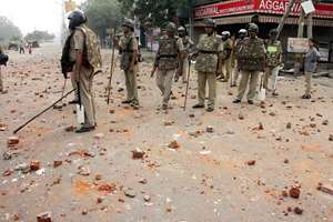 Police men patrol as brick bats are seen at a road in Trilokpuri, New Delhi, a day after a clash between two groups. Members of the Hindu and Muslim community clashed in East Delhi's Trilokpuri area on Friday evening. Police said they had to resort to firing tear gas shells and lathicharge to quell the violence.