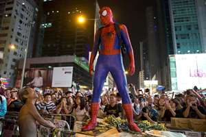 A pro-democracy protester dressed as Spider-man, stands on a barricade in the occupied area in the Mong Kok district of Hong Kong. Pro-democracy protesters in Hong Kong plan to hold a spot referendum on Sunday on whether to stay in the streets or accept government offers for more talks and clear their protest camps.