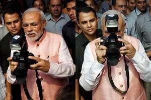 Combo: Prime Minister Narendra Modi clicks photographs during the Diwali Mangal Milan programme at BJP headquarters in New Delhi.