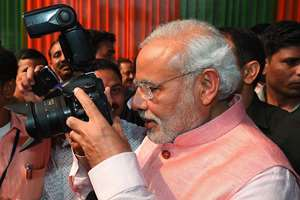 Prime Minister Narendra Modi clicks photographs during the Diwali Mangal Milan programme at BJP headquarters in New Delhi.