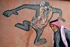 An elderly man walks past a cartoon character painted on a school wall in Suruc, near the Turkey-Syria border, across from the Syrian town of Kobani.