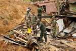 Sri Lankan army soldiers watch rescue operations at the site of a mudslide in at the Koslanda tea plantation in Badulla district, about 220 kilometers east of Colombo, Sri Lanka.