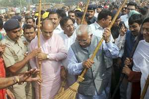 Haryana CM Manohar Lal Khattar sweeps the road after launching 'Swachh Bharat Abhiyan' campaign on Haryana Day in Faridabad.