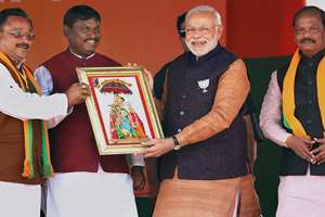 Prime Minister Narendra Modi is presented a portrait by BJP leader Arjun Munda at an election rally at Daltonganj in Palamu district, Jharkhand.