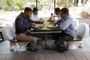 People sitting on commode-seats at the Toilet Café inside Environmental Sanitation Institute (ESI) in Ahmedabad.