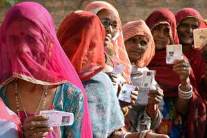 Voters showing their voter ID cards outside a polling booth during local municipal elections in Bikaner.
