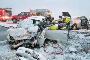 Douglas County firefighters work to get two occupants out of a car after a head-on collision between two vehicles near Rock Island, Washington, during a snowstorm. A reported total of six people were injured in the accident that blocked traffic in both directions.