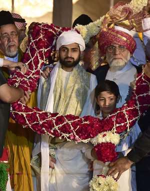 Shaban Bukhari (C), the son of Delhi's Jama Masjid Shahi Imam Syed Ahmed Bukhari (R) being garlanded after being formally anointed the Naib Imam of the 17th century mosque at a ceremony in New Delhi.