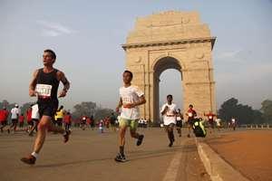 Participants of Delhi Half Marathon run past the India Gate war memorial in New Delhi.