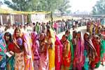 Voters wait to cast their votes at a polling station during the first phase of Jharkhand assembly election, in Latehar.