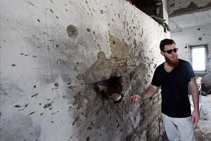 Chief of Security at Nariman (Chabad) House, Naftali Charter points towards a wall damaged by firing, on the sixth anniversary of the 26/11 terror attacks, in Mumbai.