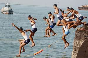 Officers of Indian Navy jump in Arabian sea for 100 meter swimming competitions as part of Navy Week celebrations in Jamnagar.