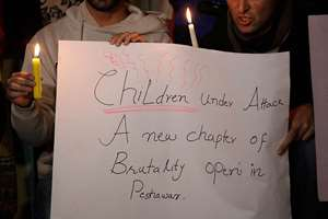 Pakistani civil society members take part in a candle light vigil for the victims of a Taliban attack on a school in Peshawar, in Islamabad, Pakistan.