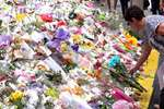 A woman places a floral tribute at a temporary memorial site close to the Lindt Chocolat Cafe in Sydney, Australia.