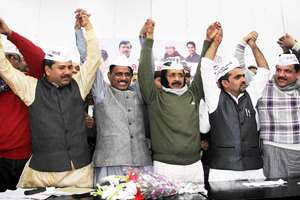 AAP convener Arvind Kejriwal raises hands with former BJP leader Umesh Verma who along with his supporters joined Aam Aadmi Party in New Delhi.