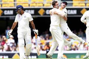 Australia's Josh Hazlewood, centre, celebrates with David Warner, right, after getting the wicket of MS Dhoni, left, during play on day four of the second cricket test between Australia and India in Brisbane, Australia. A listless India capitulated to a four-wicket defeat in the second cricket Test against Australia with an inept batting display by the top-order to give the hosts an invincible 2-0 lead in the four-match series.