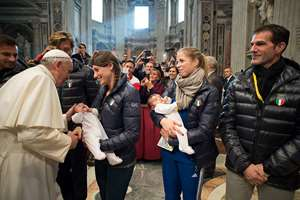 In this photo provided by Vatican newspaper L'Osservatore Romano, Pope Francis caresses a baby as Italian former luger Armin Zoeggeler, right, and former figure skating world champion Carolina Kostner, second from right, look on, after a Mass for members of the Italian Olympic Committee to mark their 100th anniversary in St. Peter's Basilica at the Vatican. Pope Francis has given a papal thumbs up to Rome's bid for the 2024 Summer Olympics amid talk that the Vatican might host some events. But he is warning: I won't be around.