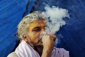 A Sadhu smokes a marijuana pipe on a cold morning at Sangam, in Allahabad.