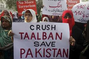 Supporters of Pakistan Awami Tehreek hold up posters to condemn the Taliban attack on a military-run school in Peshawar.