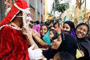Children enjoy with Santa Claus ahead of Christmas Day celebrations, in Kolkata.