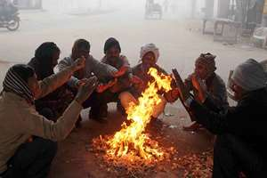 People sit around a bonfire to warm themselves during a chilly morning, in Allahabad.