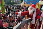 A man dressed as Santa Claus distributes chocolates to the children on the occasion of Christmas, at St. Joseph Church in Guwahati.