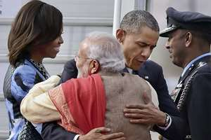 Prime Minister Narendra Modi hugs visiting US President Barack Obama as first lady Michelle Obama looks on upon their arrival at Air Force station Palam, in New Delhi.
