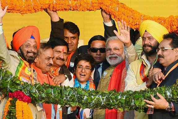 Prime Minister Narendra Modi and BJP CM candidate Kiran Bedi being garlanded during an election rally at Karkarduma, in New Delhi.
