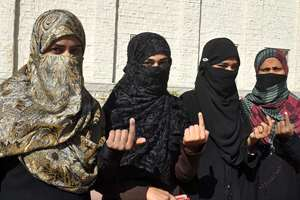 Muslim women show their inked fingers after casting their votes for Local Body Elections in Bhopal.