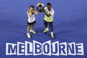 Martina Hingis of Switzerland, left, and Leander Paes hold up the trophy after defeating Kristina Mladenovic of France and Daniel Nestor of Canada in the mixed doubles final at the Australian Open tennis championship in Melbourne, Australia.
