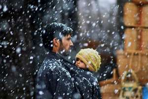 A Kashmiri man carries his daughter as he walks on a snow-covered road closed due to heavy snowfall at Qazigund in Anantnag district.