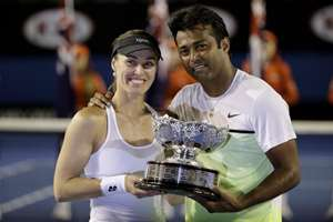 Martina Hingis of Switzerland, left,  and Leander Paes of India hold trophy after defeating Kristina Mladenovic of France and Daniel Nestor of Canada in the mixed doubles final at the Australian Open tennis championship in Melbourne, Australia.