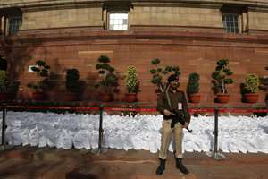 Paramilitary soldier stands guard near copies of the Railway Budget for the year 2015-16 to be distributed to lawmakers and officials at the parliament house in New Delhi.