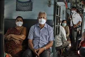 Passengers wear a protective mask as they sit in a train compartment in Ahmadabad.