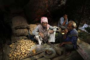 Vendors selling potatoes at a wholesale vegetable market drink tea as they wait for customers in Allahabad.