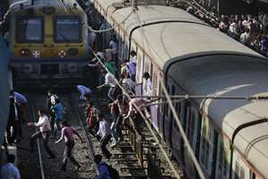 Commuters cross railway tracks to catch trains at a railway station in Mumbai.