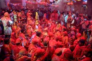 People celebrate Holi at Barsana Temple in Mathura.