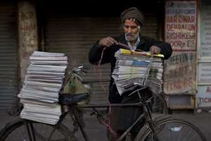 Newspaper vendor ties newspapers on his bicycle early in the morning at the old city area of New Delhi.