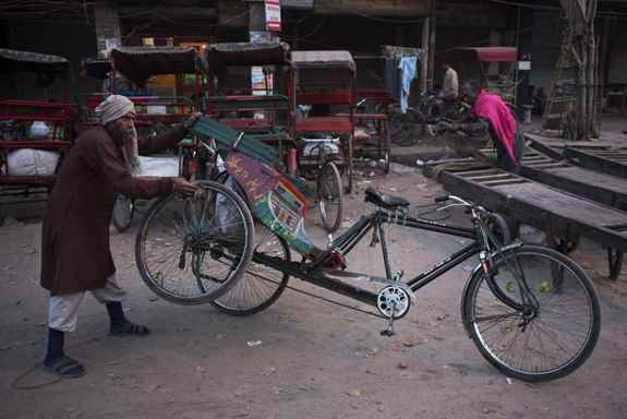A laborer cleans a cycle rickshaw, early morning in New Delhi.