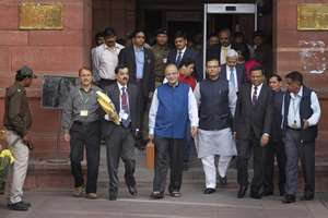 Finance Minister Arun Jaitley, center in blue jacket, carries a briefcase containing union budget for the year 2015-16 as he leaves his office for Parliament to present the union budget in New Delhi.