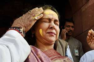 BJP MP Hema Malini reacts as an MP smears Gulal on her forehead ahead of Holi celebrations, at Parliament House in New Delhi.