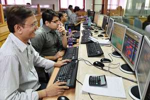 Traders at the Bombay Stock Exchange react with jubilation as the Sensex crosses the 30,000 mark in Mumbai.