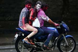 Men, their faces smeared with colored powder, ride a motorbike on Holi, in Hyderabad.