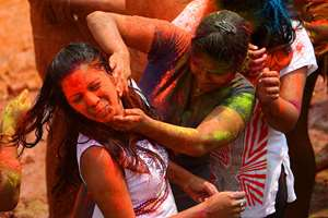 Girls throw colored powder on each other during Holi celebrations, in Hyderabad.