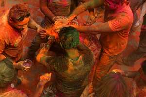 People smear colored powder on a girl during Holi celebrations in Hyderabad.