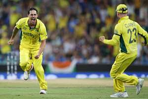 Australia's Mitchell Johnson celebrates with his captain Michael Clarke after taking the wicket of Virat Kohli during the Cricket World Cup semifinal in Sydney, Australia.