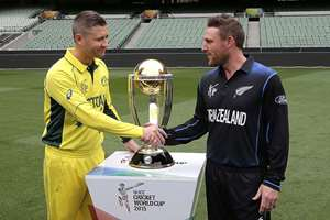 Australia's captain Michael Clarke, left, and New Zealand's captain Brendon McCullum shake hands as they pose for a photo with the Cricket World Cup trophy at the MCG in Melbourne, Australia. New Zealand will tackle Australia in the Cricket World Cup final on Sunday 29 March 2015.