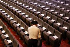 An army officer arranges funeral service programs on seats ahead of a state funeral for the late Lee Kuan Yew, at the University Cultural Center, Singapore.